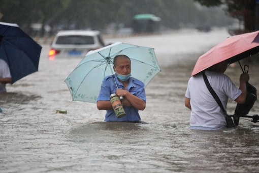 Residents wade through floodwaters on a flooded road amid heavy rainfall in Zhengzhou, Henan province, China.