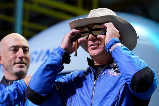 Jeff Bezos puts goggles over his eyes that belonged to aviator Amelia Mary Earhart as his brother Mark looks on. (AP Photo/Tony Gutierrez)