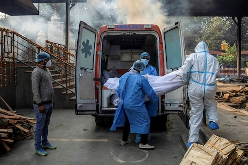 Health workers and a relative carry the body of a man, who died due to COVID-19, from an ambulance to a crematorium in New Delhi. (Reuters)