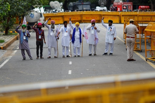 Farmers shout slogans during a sit-in protest against the farm laws, near the parliament house in New Delhi. (Reuters)