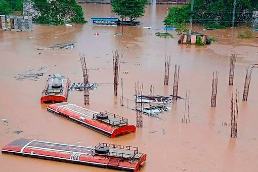 Buses submerged in a flood affected area following heavy rains, at Chiplun in Ratnagiri district, Thursday. (PTI Photo)