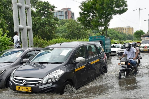 Commuters wade through a waterlogged Ring Road in New Delhi. PTI