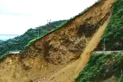 The video shows a large part of a hilltop collapsing as boulders and rocks roll downhill.