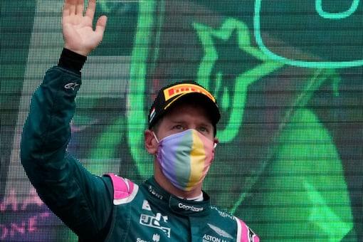 Aston Martin driver Sebastian Vettel of Germany waves on the podium after the Hungarian Formula One Grand Prix (AP)