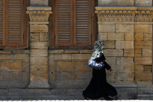 FILE PHOTO: A woman wearing a protective mask walks in front of the Max Denso Hall and Library, built in memory of Max Denso during the British colonial period, as the outbreak of the coronavirus disease (COVID-19) continues, in Karachi, Pakistan April 23, 2021. REUTERS/Akhtar Soomro