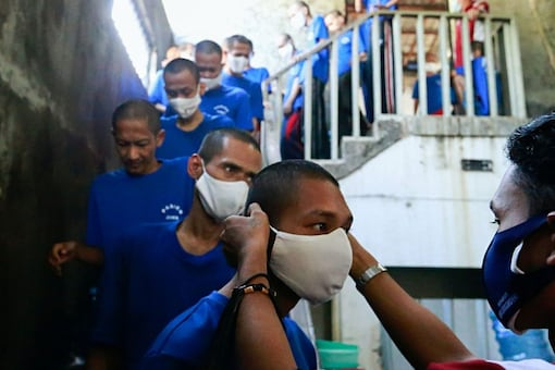 A mental health officer provides a protective face mask to a patient suffering from mental illness during a vaccination program in Bekasi, on the outskirts of Jakarta, Indonesia. (Reuters/for representation)