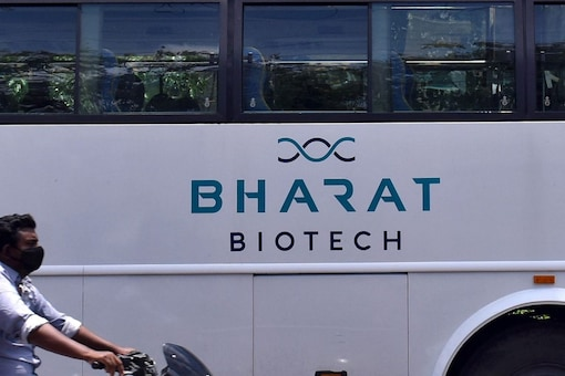 A man rides his motorbike past a parked bus of India's biotechnology company Bharat Biotech outside its office in Hyderabad, India July 3, 2020. REUTERS/Stringer