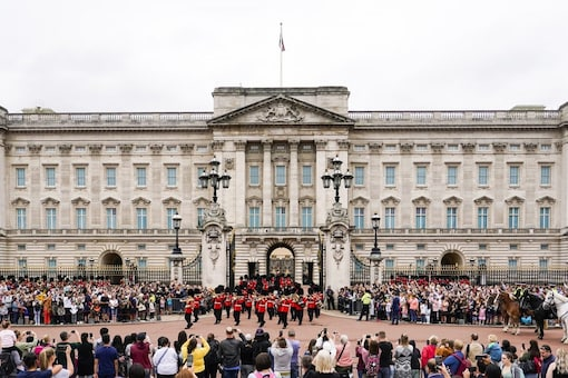 Members of the public watch the Changing of the Guard ceremony at Buckingham Palace, London, Monday August 23, 2021. (AP)