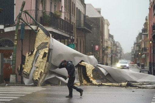 A man passes by a section of roof that was blown off of a building in the French Quarter by Hurricane Ida winds. (AP)