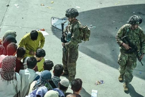 US soldiers stand guard as Afghan people wait at Kabul airport earlier this week.  (AFP)