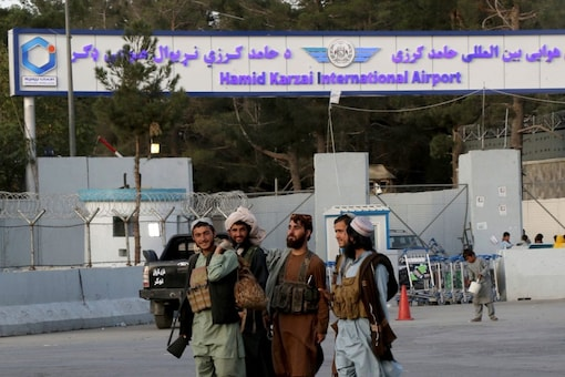 Taliban fighters walk in front of the gate of Hamid Karzai international Airport in Kabul, Afghanistan. (Photo: AP)