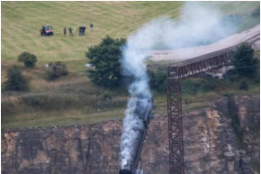 A new BTS clip from Mission: Impossible set shows a train crashing from a cliff into a valley