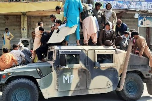 Taliban fighters and local residents sit over an Afghan National Army (ANA) humvee vehicle along the roadside in Laghman province on August 15, 2021. (AFP)