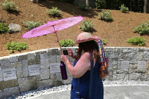 Karla Hailer, a fifth-grade teacher from Scituate, Mass., shoots a video where a memorial stands at the site in Salem, Mass., where five women were hanged as witches more than 325 years earlier. (Image Credits: AP)
