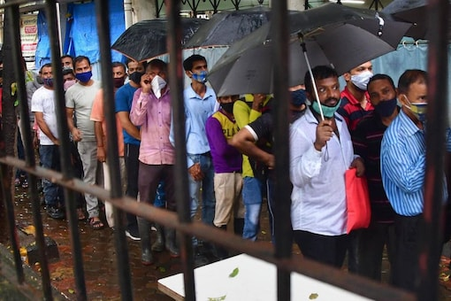 People wait to receive a dose of COVID-19 vaccine during mass vaccination drive at Lalbaug area in Mumbai. (PTI)