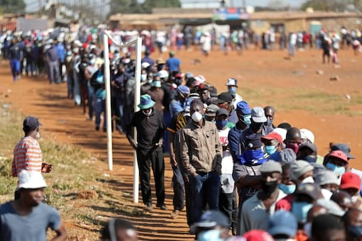 People wearing protective face masks stand in a queue to receive food aid amid the spread of the coronavirus disease (COVID-19) outbreak, at the Itireleng informal settlement, near Laudium suburb in Pretoria, South Africa, May 20, 2020. REUTERS/Siphiwe Sibeko/File Photo