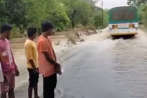 Locals watch as the driver tries to navigate the bus through a submerged bridge. (News18)
