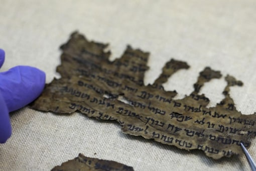A conservator of the Israel Antiquities Authority (IAA) shows fragments of the Dead Sea Scrolls at their laboratory in Jerusalem on June 2, 2020.  (Credits: AFP)