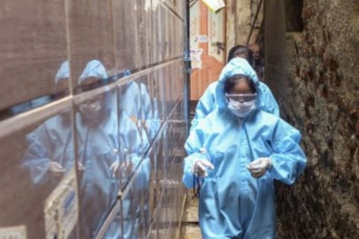 Health workers wearing PPE walk through a narrow lane of the Dharavi slum during a door-to-door Covid-19 screening in Mumbai. (Image: Reuters)