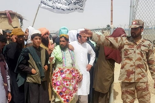 A Pakistani paramilitary soldier controls people waiting with a Taliban's flag to welcome a man wearing who, according to them, was released from prison in Afghanistan. (File photo: Reuters)