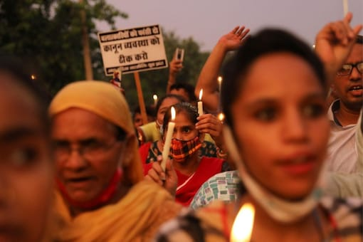 People attend a candlelight vigil to protest against a rape case in Delhi. (Image Credits: Reuters)