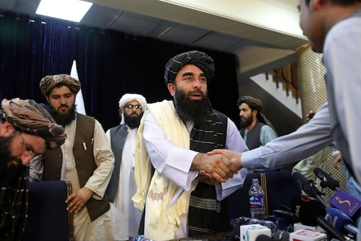 FILE - In this Aug. 17, 2021, file photo, Taliban spokesman Zabihullah Mujahid, shakes hands with a journalist after his first news conference, in Kabul, Afghanistan. (AP)