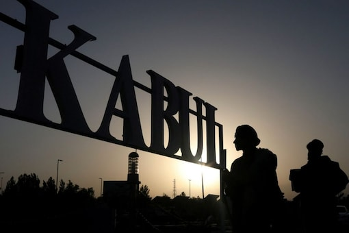 Taliban soldiers stand in front of a sign at the international airport in Kabul, Afghanistan, (Reuters)