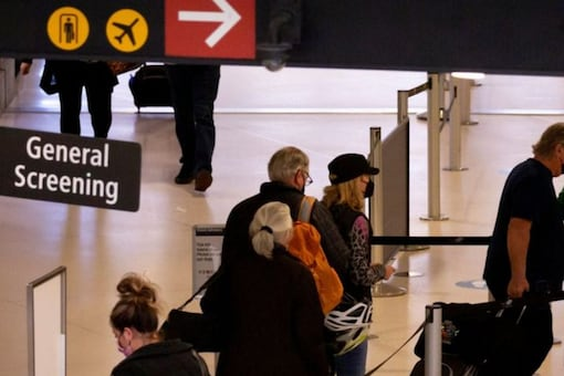 Travelers go through general screening at a security checkpoint at Seattle-Tacoma International Airport in SeaTac, Washington, U.S. April 12, 2021. REUTERS/Lindsey Wasson