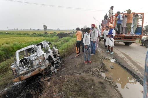 Lakhimpur Kheri violence: People take a look at the overturned SUV which was destroyed in Sunday's violence during farmers' protest at Tikonia area of Lakhimpur Kheri district. (PTI)