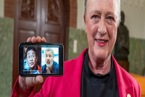 Chair of the Norwegian Nobel Peace Prize Committee Berit Reiss-Andersen shows on a mobile phone photo of laureates of the 2021 Nobel Peace Prize, journalists Maria Ressa and Dmitry Muratov, in Oslo, Norway October 8, 2021.  (NTB/Heiko Junge via REUTERS)
