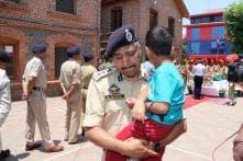 Slain Colleague's Son in Arms, Cop Breaks Down at Wreath-laying Ceremony