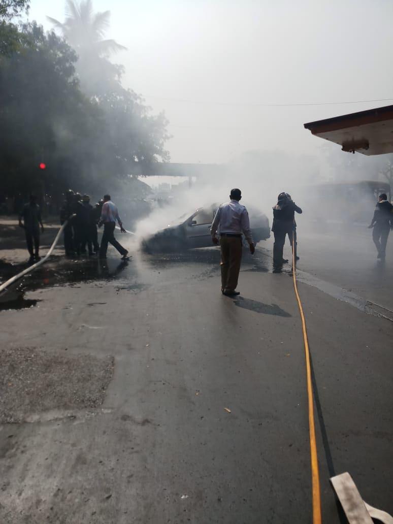 पेट घेतलेल्या कारच्या आगीवर नियंत्रण मिळवताना अग्निशामक दलाचे कर्मचारी.