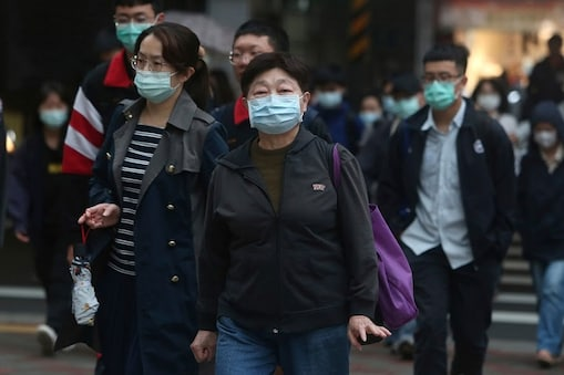 People wearing face masks to protect against the spread of the new coronavirus walks on a street in Taipei, Taiwan, Monday, March 30, 2020. The new coronavirus causes mild or moderate symptoms for most people, but for some, especially older adults and people with existing health problems, it can cause more severe illness or death. (AP Photo/Chiang Ying-ying)