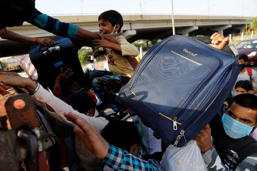 नवी दिल्ली - प्रवासी मजुरांनी ट्रकमध्ये चढण्यासाठी गर्दी केली होती. अक्षरश: मुलं आणि त्यांचे सामान ढकलून ट्रकमध्ये चढवण्यात आलं. टा ट्रक त्यांना त्यांच्या घरी उत्तर प्रदेशमध्ये नेणारा होता (फोटो सौजन्य- Reuters)