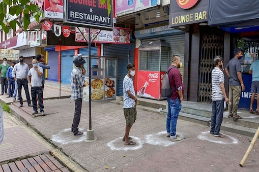 Guwahati: People maintain social distance as they stand in a queue to buy alcohol from a wine shop, during the ongoing COVID-19 pandemic, in Guwahati, Saturday, May 2, 2020. (PTI Photo)(PTI02-05-2020_000233B)