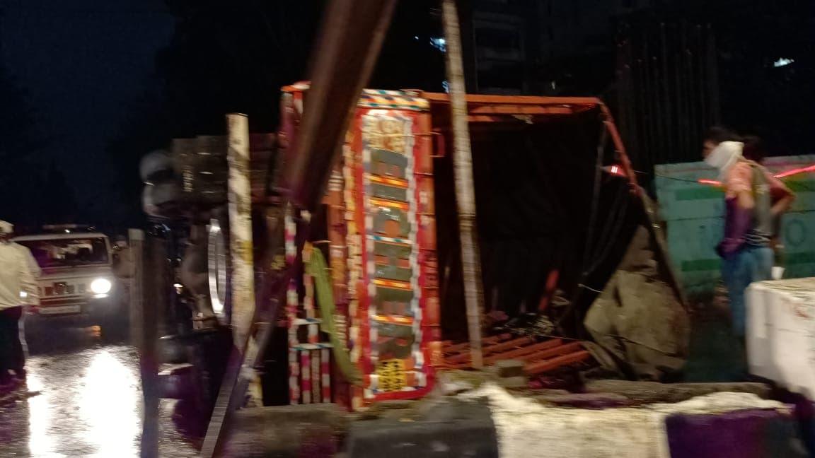 भर रस्त्यातच चालकाचा ताबा सुटून ट्रक उलटला.