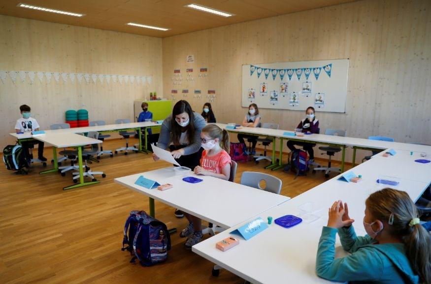 ऑस्ट्रेलियातील या शाळेत शिक्षक विद्यार्थीनीशी बोलत आहेत. ही मुलं एकमेकांच्या अगदी जवळ नाहीत. शिवाय या सर्वांनी मास्क घातला आहे.(Image: Reuters)