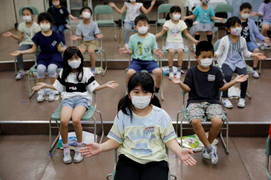 जपानच्या टाकानेदाई दैसेन एलेमेंट्री स्कूलमधील म्युझिक क्लास सुरू असताना मुलं अशी आवश्यक ती सोशल डिस्टन्सिंग ठेवत गाणी गात आहेत, टाळ्या वाजवत आहेत.(Image: Reuters)