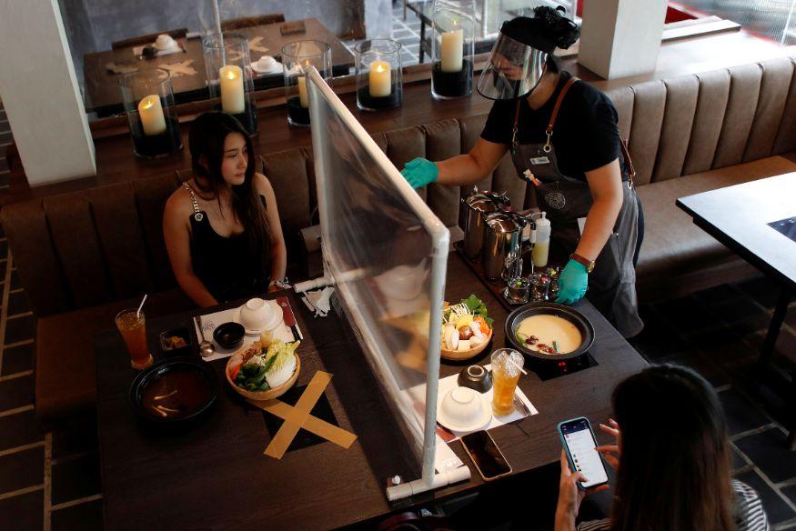 थायलंडच्या बँकॉकमधील थायवानीझ हॉट पॉट स्टाइल रेस्टॉरंटमध्ये एका टेबलवर अशा पद्धतीने ग्लास टाकून दोन भाग पाडण्यात आले. टेबलवर समोरासमोर आणि शेजारी अशा पद्धतीने कुणी बसणार नाही. तर क्रॉस सेक्सशनमध्ये बसण्याची सोय करण्यात आली आहे. वेटर्सही फेस शिल्ड आणि ग्लोव्ह्ज घालून सर्व्हिस देत आहेत.(फोटो सौजन्य - रॉयटर्स)