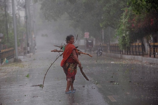 An Indian woman collects tree branches fallen on a road after a heavy downpour during lockdown in Gauhati, India, Wednesday, April 15, 2020. Indian Prime Minister Narendra Modi on Tuesday extended the world's largest coronavirus lockdown to head off the epidemic's peak, with officials racing to make up for lost time. (AP Photo/Anupam Nath)
