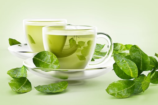 Glass cups with green tea and tea leaves isolated on white.