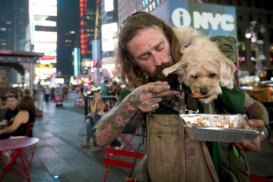 Deke Breuer feeds his dog Cahlupa in Times Square in the Manhattan borough of New York. ಪ್ರಾಣಿ ಪ್ರಿಯರಾದ ದೆಕೆ ಬ್ರುಯರ್ ಅವರು ನ್ಯೂಯಾರ್ಕ್ನ ಮ್ಯಾನ್ಹಟನ್ನಲ್ಲಿ ತಮ್ಮ ನಾಯಿಗೆ ಆಹಾರ ತಿನ್ನಿಸುತ್ತಿರುವುದು.