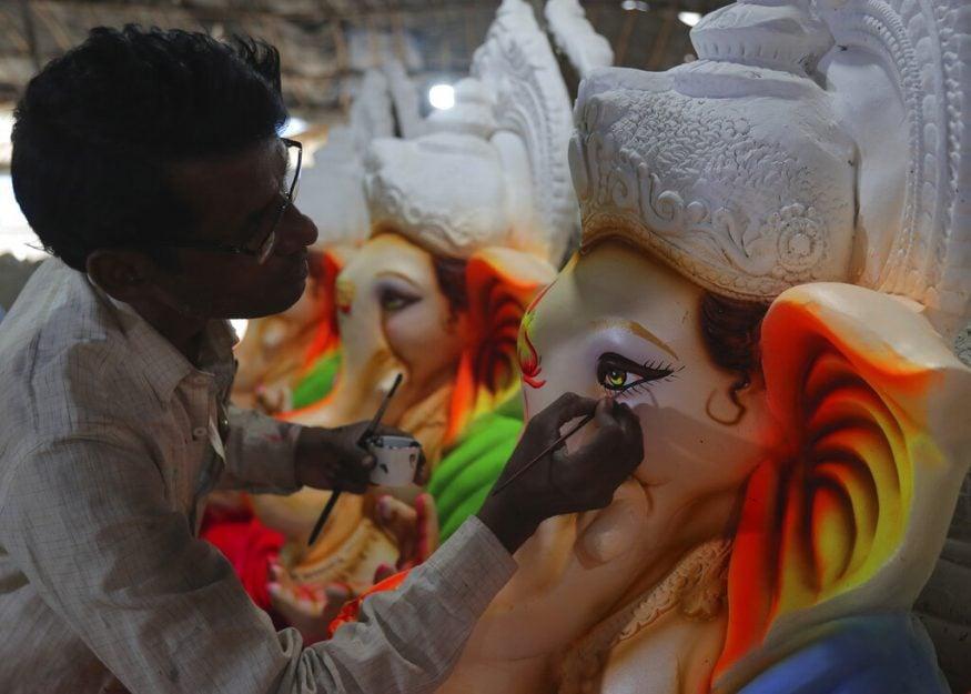 ഹൈദരാബാദിൽ ഗണേശ വിഗ്രഹത്തിൽ പെയിന്റിംഗ് ജോലികൾ പൂർത്തിയാക്കുന്ന കലാകാരൻ. (Image: AP)