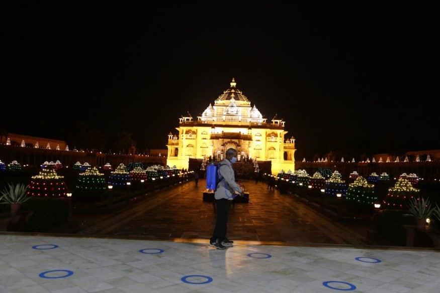ഗുജറാത്ത് ഗാന്ധിനഗറിലെ അക്ഷർധാം ക്ഷേത്രത്തിന് മുന്നിൽ അണുവിമുക്തമാക്കുന്നു. രാജ്യമെമ്പാടും ഇന്ന് ദീപാവലി ആഘോഷിക്കുകയാണ്. (Image: AP)