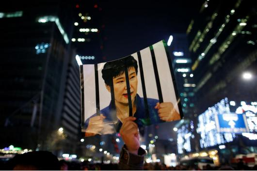 A man holds up a picture bearing an image of South Korean President Park Geun-hye as he attends a ceremony to celebrate the new year after a protest demanding Park's resignation, in Seoul. Photo: Reuters