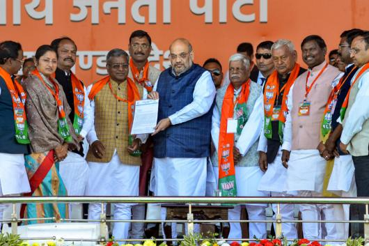 Ranchi: Union Home Minister Amit Shah (C) receives a memorandum from MP's of Jharkhand state during a 'samaroh' program to merge Jharkhand Vikas Morcha (Prajatantrik) party and Bharatiya Janata Party, at Prabhat Tara ground in Jagannathpur area of Ranchi, Monday, Feb. 17, 2020. (PTI Photo)