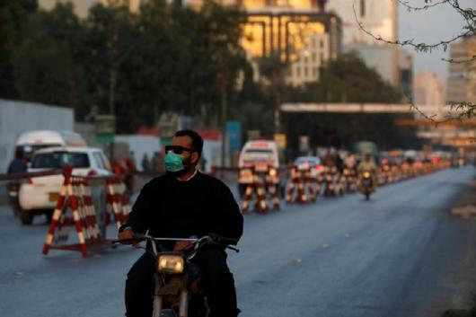 A man wears a face-mask as a preventive measure following the coronavirus outbreak, as he rides on motorbike in Karachi, Pakistan. (Reuters)