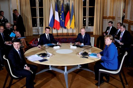 French President Emmanuel Macron and Russian President Vladimir Putin attend a working session with German Chancellor Angela Merkel and Ukrainian President Volodymyr Zelenskiy at the Elysee Palace, in Paris, France, on Monday. (Reuters)