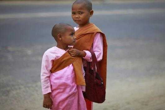 Buddhist novice nuns wait for a bus at a bus stop in Yangon, Myanmar. (Image: Reuters)