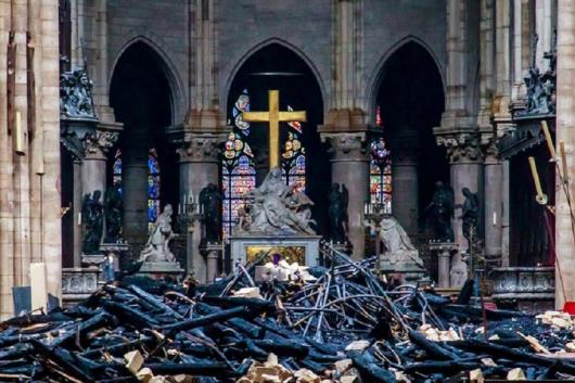 A view of the cross and sculpture of Pieta by Nicolas Coustou in the background of debris inside Notre-Dame de Paris, in the aftermath of a fire that devastated the cathedral, during the visit of French Interior Minister Christophe Castaner in Paris. (Image: Reuters)